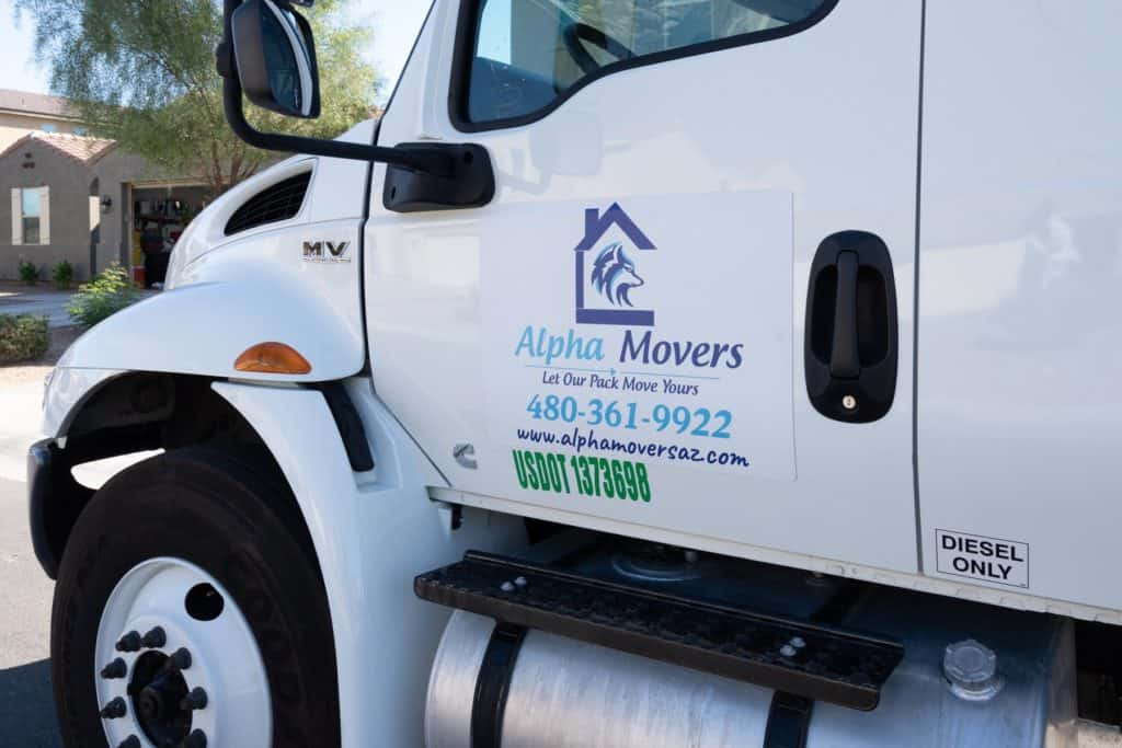 Image: A white Alpha Movers trucks with outside business sticker.