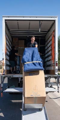 This image shows an Alpha Movers crew member unloading a moving truck.