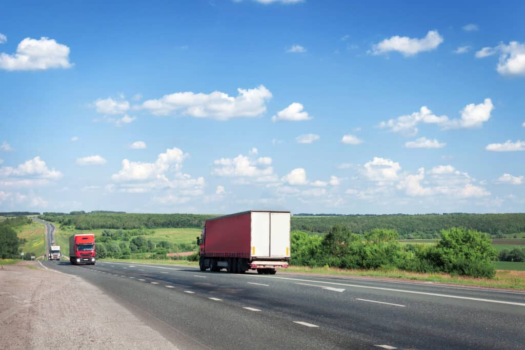 Trucks and cars drive along the summer road, the highway.
