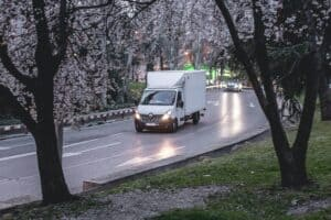 A white moving truck driving at dusk